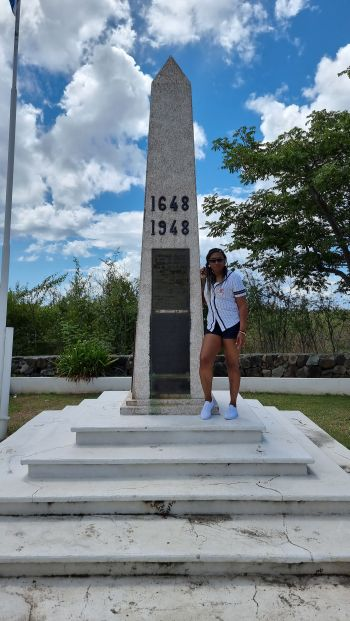 Maxine Simms-Famous stands at the border between Saint Martin and Sint Maarten. Photo: Provided