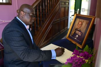 House Speaker, Hon Julian Willock signs the book on condolences in the Virgin Islands. Photo: Team of Reporters