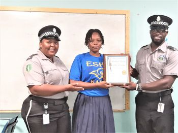 Road Town Community Officer Mitchell John and his colleague Constable Emnisa Edwards presented a certificate for the community spirit shown by Elmore Stoutt High School student Swelend Charles. Photo: RVIPF