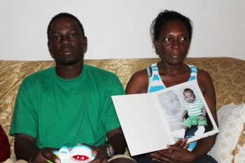 Orvan C. Moses, the mother of eleven month old Jakewon C. O. Pompey, shows reporters a photo of their child. At left is Clavis H. Pompey. The grieving parents say the want answers from the relevant authorities on what really occurred on that tragic day. Photo: VINO