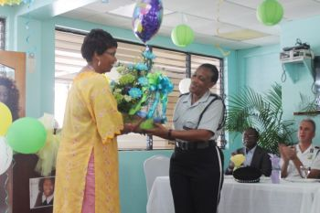 Superintendent of Police Jacqueline E. Vanterpool is presented with a bouquet. Photo: VINO