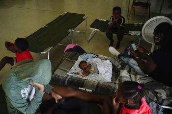Anastacia Makey, 43, far right, looks at her phone as she and her family sits on cots with other residents inside a church that was opened up as a shelter as they wait out Hurricane Dorian in Freeport on Grand Bahama, Bahamas on Sunday. — AP Photo/Ramon Espinosa