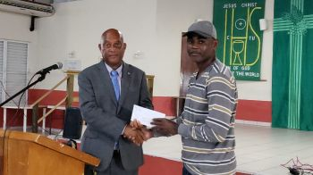 Ninth District Representative and Minister for Natural Resources, Labour and Immigration, Honourable Vincent O. Wheatley (R9), left, presents a cheque for $1000.00 to Mr Sam Alexander of the Virgin Gorda Music School. Photo: VINO