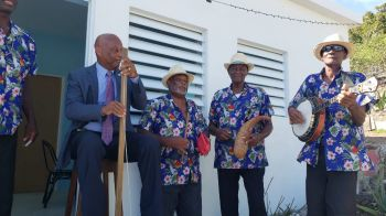 Minister for Natural Resources, Labour and Immigration, Honourable Vincent O. Wheatley (R9) shows off his musical skills at the handing over of the keys to Mr Anderson Hamm's home on December 24, 2019. Photo: Facebook