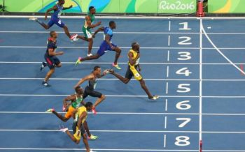 Usain Bolt starts celebrating as he crosses the finish line. Photo: GETTY IMAGES