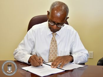 Premier and Minister of Finance, Dr. The Honourable D. Orlando Smith, OBE signing agreement between the Government and UNDP. Photo: Franklyn Skerritt