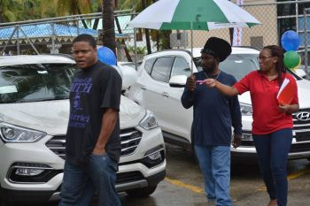 A potential customer being taken through the line of vehicles on offer by Tortola Auto Group. Photo: Provided