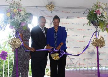 The ceremonial cutting of the ribbon: (L-R) Asha A. Black, Bougainvillea Clinic Manager Dr Heskith Vanterpool and Mrs Vanterpool. Photo: VINO