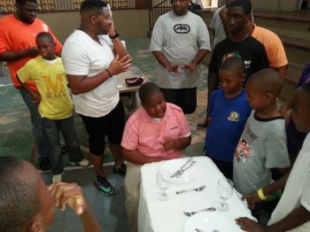 The young men learned the ins and outs of properly setting a dinner table from the utensils to be used in the main course to those for desserts and appetizers. Leading the guidance in this area was Kareem-Nelson Hull. Photo: VINO