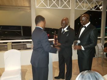 Mr Salvadol E. Callwood, fondly known as Brother Sal, receives his plaque from Pastor Leriano Webster (right). Photo: VINO