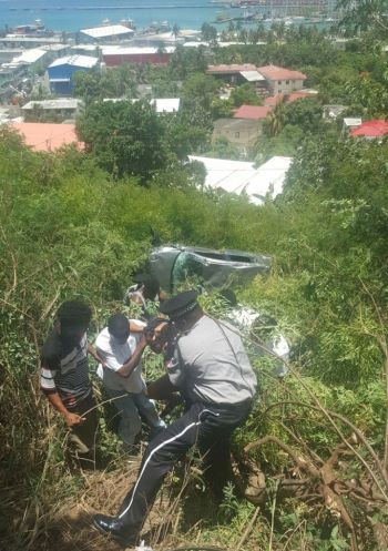 Police and public spirited citizens assist a passenger involved in an accident at Free Bottom today, June 24, 2017. Photo: Provided