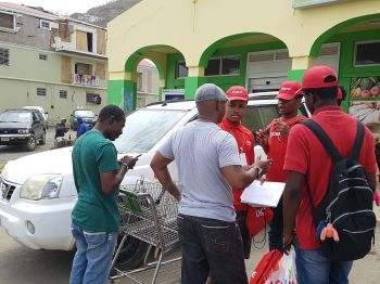 Digicel workers speaking to members of the community and distributing free sim cards. Photo: Provided