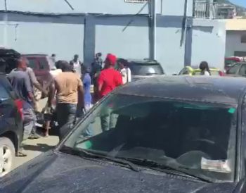 Persons trying to restrain the irate man outside BVI Communications. Photo: Team of Reporters
