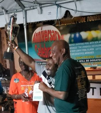 Leroy Jones, centre, proudly lifts the trophy as the winner of the 2nd Annual Kenroy C. Millington Memorial Pool Tournament in Virgin Gorda on May 5, 2019. Minister for Natural Resources, Labour and Immigration Hon Vincent O. Wheatley (R9), right, was also on hand to share in the celebration and present prizes. Photo: Provided