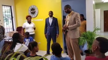 Minister for Education, Culture, Youth Affairs, Fisheries and Agriculture Dr the Honourable Natalio D. Wheatley (R7), right, addresses the children attending the Summer Programme at the Resource Centre in Huntums Ghut, Tortola. Second from right is Deputy Premier, Minister for Transportation, Works and Utilities, and Fifth District Representative Hon Kye M. Rymer. Photo: VINO