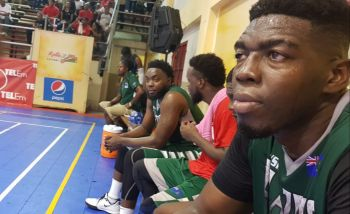 Kleon C. Penn of BVI Bayside Blazers, right, watches the game from the bench after starting the first quarter against Dominican Republic. Photo: VINO