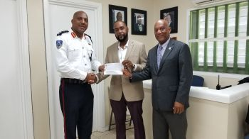 On October 1, 2019, Deputy Speaker and Territorial Member Honourable Neville A. Smith aka 'Sheep', centre, handed over a cheque of $1,500.00 to Superintendent of Prison Mr Verne Garde, left, to assist in financing the Restorative Justice Programme. Right is Deputy Premier and Minister for Natural Resources, Labour and Immigration, Honourable Vincent O. Wheatley (R9). Photo: HoA