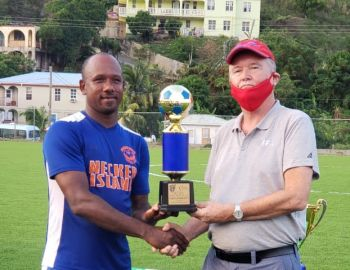 The ever dangerous Derol Redhead, left, receives the MVP trophy from BVIFA President, Andy Bickerton. Photo: VINO