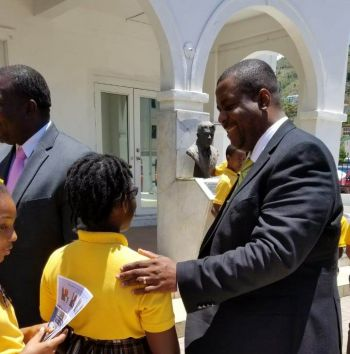 Premier and Minister of Finance Honourable Andrew A. Fahie (R1) greets a student of the Ebenezer Primary School on June 3, 2019. Photo: GIS