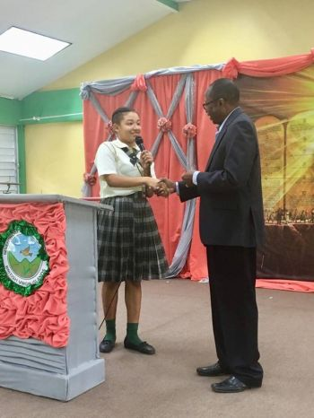 A student of the BVI Seventh-day Adventist School shows her appreciation to Third District Representative Hon Julian Fraser RA, right, for delivering on his promise of a $10,000 towards the school's computer lab. Photo: Facebook