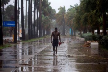A man walks under pouring rain during Storm Isaias, then a tropical storm, in Santo Domingo, Dominican Republic, on July 30, 2020. Photo: Getty Images