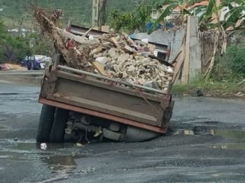 A truck that was stuck in a huge pothole in Paraquita Bay, Tortola before it was temporarily filled with stones. Photo: Team of Reporters
