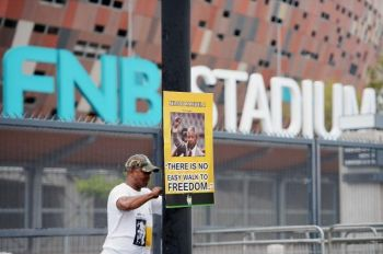 A member of the African National Congress puts up a poster of Nelson Mandela at the First National Bank Stadium in Soweto, South Africa, on Monday in preparation for former South African president's funeral on Tuesday. For workers cleaning the stadium, it was a personal mission for a hero to whom they owe their freedom. Photo: JEFF J MITCHELL/GETTY IMAGES