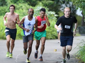 James Carr (right) battling one of the steep hills alongside (Left to Right) Guy Williamson, Ravindra Sukhu and Reuben Stoby during the Carrot Bay leg of the 2013 Ceres Juices 10K Series on September 14. Photo: Dean 'The Sportsman' Greenaway