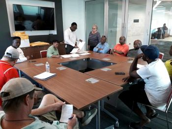 Director of Procurement of the Virgin Islands Recovery and Development Agency (RDA) Mr John Primo, standing, left, announces the commercial packages in the tenders for the removal of derelict boats in the Virgin Islands. Photo: RDA/Colene A. Penn