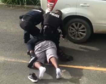 Two officers of the Royal Virgin Islands Police Force wrestle the young man to the ground before handcuffing him on September 27, 2020. Photo: VINO/File