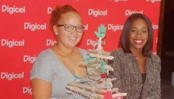 From left: Alexandra V. Durante of Tree of Hands and Katasha Melville, the PR and Sponsorship Executive of Digicel BVI, pose with a driftwood Christmas 'Tree of Hands' at the launching of the 2015 Tree of Hands initiative at Bamboushay Lounge in Road Town on November 26, 2015. Photo: VINO/File