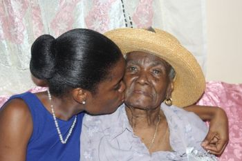 Businesswoman and former Miss BVI Sharie B. Y. de Castro kisses her grandmother, Josephine Rhymer, during Mr and Mrs Rhymer's 73rd wedding anniversary celebrations back in September 2013. Photo: VINO/File