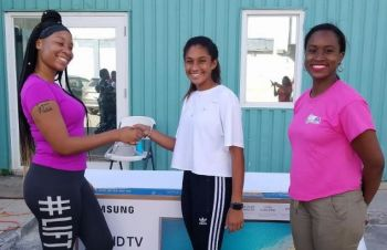 Ariel Mohamed (centre) presents the Samsung Smart TV sponsored by Klass Electronics to Ms Lakeisha Claxton (left) in the One Mart Parking Lot on Saturday November 17, 2018. At right is Director of FSN Mrs Sasha Stoutt. Photo: Provided