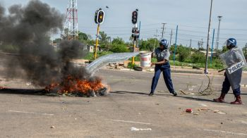 A policewoman puts out a fire lit by protesters in Bulawayo. Photo: Al Jazeera