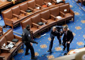 Members of Congress run for cover as protesters attempt to enter the House Chamber. Photo: Getty Images