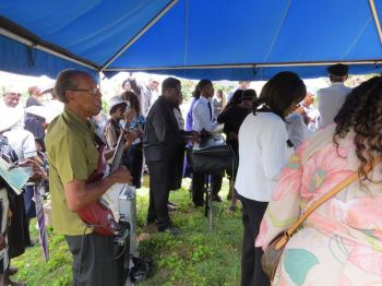 Friends and family members at the burial ground singing hymns accompanied by a full band of keyboardist, guitarist and tambourines. Photo: Provided