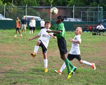 A player from St George's Primary School bravely heads the ball away from two opposing players of Cedar School. Photo: Charlie E. Jackson/VINO
