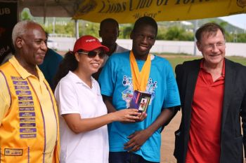 Shemay Maning, 2014 Top Athlete at the 10th Annual Special Needs Games with the Governor, John S. Duncan OBE (right), Tortola Lion's Club President Mr. Hesketh Newton (left) and Alejandra Casares of Digicel. Photo: Charlie E. Jackson/VINO