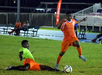 A Sugar Boyz player evades a sliding tackle by a One Love player. Photo: Charlie E. Jackson/VINO