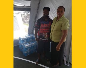 Mrs Pearlette Frazer-Smith (right), Principal of Leonora Delville Primary School and a representative from Tatoo's Trucking donating cases of water to the primary school. Photo: Provided