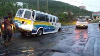 A taxi was seen stuck in one of the many pot holes across the territory. Photo: Facebook