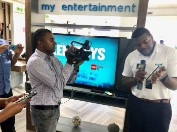 Mr Akeen Merry, the FLOW BVI Retail Store Manager, explaining one of its services up for the Christmas Promotion. Photo: Team of Reporters