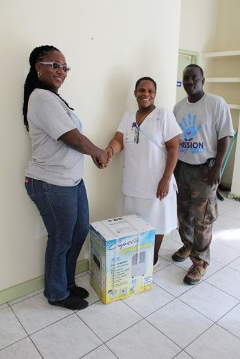 Members of the Flow Missions Day team also donated a dehumidifier for the North Sound Clinic nursing residence, which was presented to Nurse Rosalind Daisy. The donation was made as part of the company's Mission Day community service activities. Photo: Flow