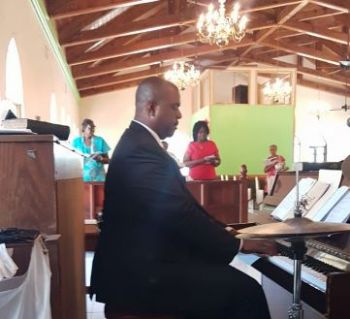 Premier Fahie playing an organ at a church in his District. Photo: Team of Reporters