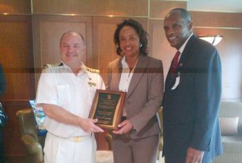 Captain Philpott (left) is presented with a plaque by Director of Operations at port agent representatives Romney Associates Consultant, Ms Patricia Romney. Also in picture is Minister for Communications and Works Hon. Mark Vanterpool. Photo: VINO