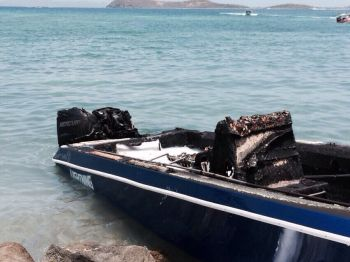 Officers from the Virgin Islands Fire and Rescue Services, with the aid of persons on other boats, were successful in putting out a fire believed to be from an explosion on a powerboat on Beef Island today May 24, 2015. Photo: Team of Reporters