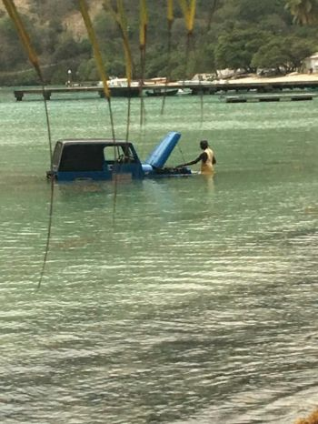 According to reports from Jost Van Dyke, the driver of the vehicle had lifted the bonnet of the vehicle to check his engine and then proceeded to start the vehicle unaware that the vehicle was in gear. The vehicle quickly reversed into the water. Photo: Team of Reporters