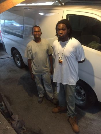 Mr Akeil A. Howell with one of his employees of Connie's Garage. Photo: Provided