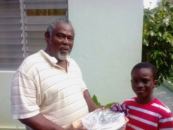 A resident of Hannah's Estate receives his are basket from Elijah Mc Lean (right). Photo: Provided