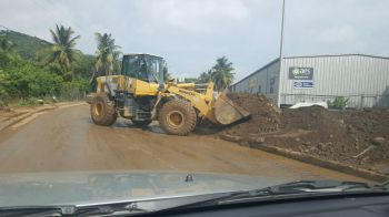 Crew cleaning up in Pasea. Public Works crews as well as private heavy equipment operators have been out cleaning roads and moving abandon vehicles, mud, rocks, tress, garbage and other debris from roadways. Photo: Team of Reporters